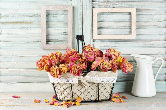 Shabby chic still life: bunch of vintage pink dry roses in wire basket and jug against white wooden blinds with empty photoframes. - 87491877